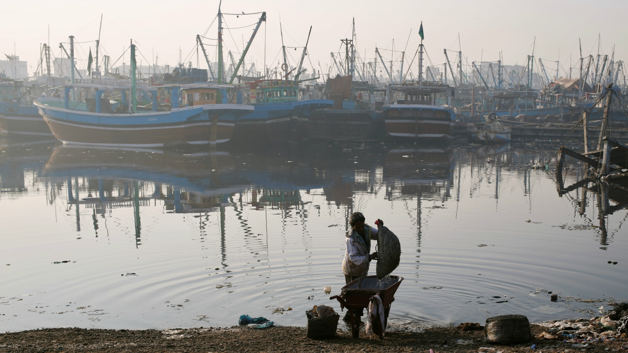 A labourer washes his wheelbarrow with a basket of water while working next to a harbour for fishing boats, in Karachi, Pakistan. (Reuters)