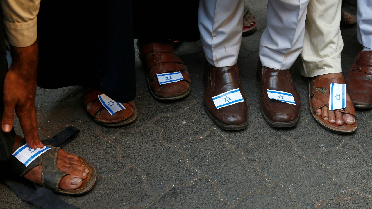 People stick Israeli flags on their shoes during a protest against the visit of Israeli Prime Minister Benjamin Netanyahu, in Mumbai. (Reuters)