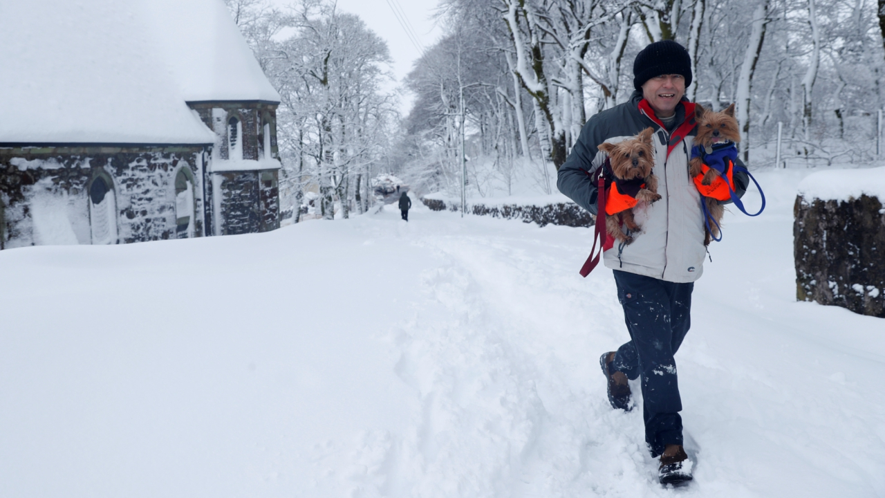 A man carries his dogs in Leadhills, Scotland, Britain. (Reuters)