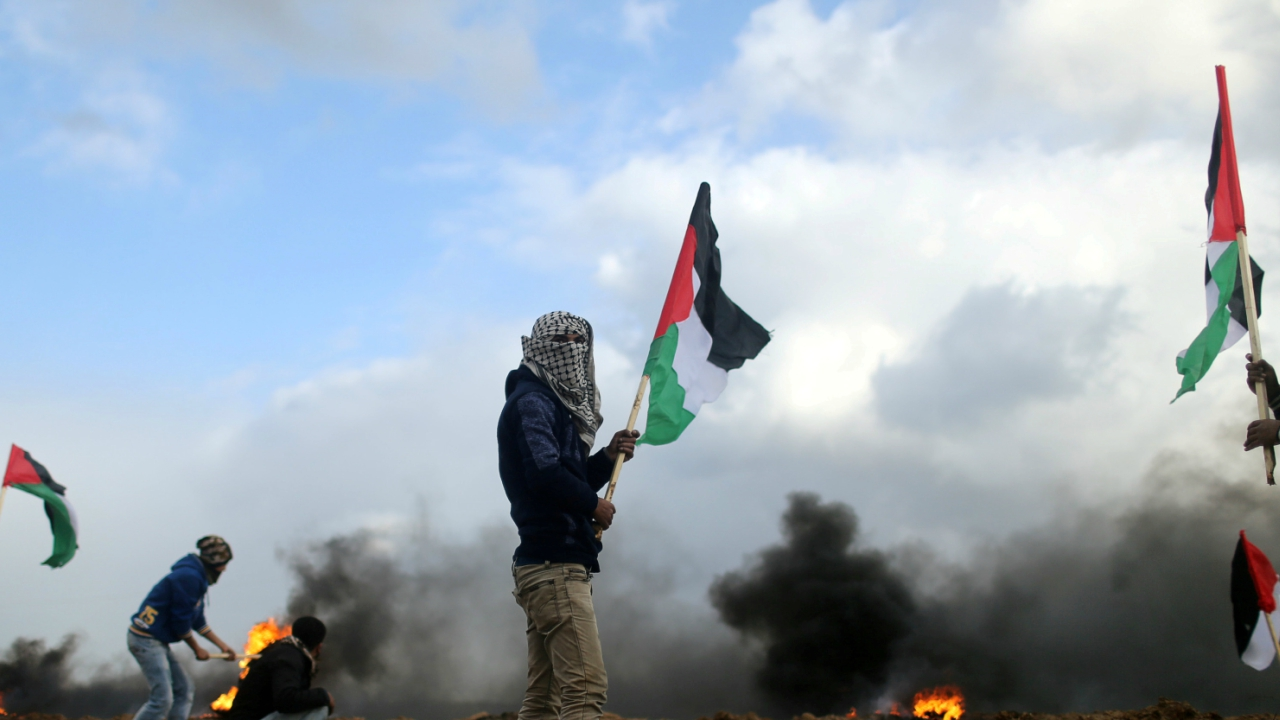 A demonstrator holds a Palestinian flag during clashes with Israeli troops, near the border with Israel in the southern Gaza Strip. (Reuters)