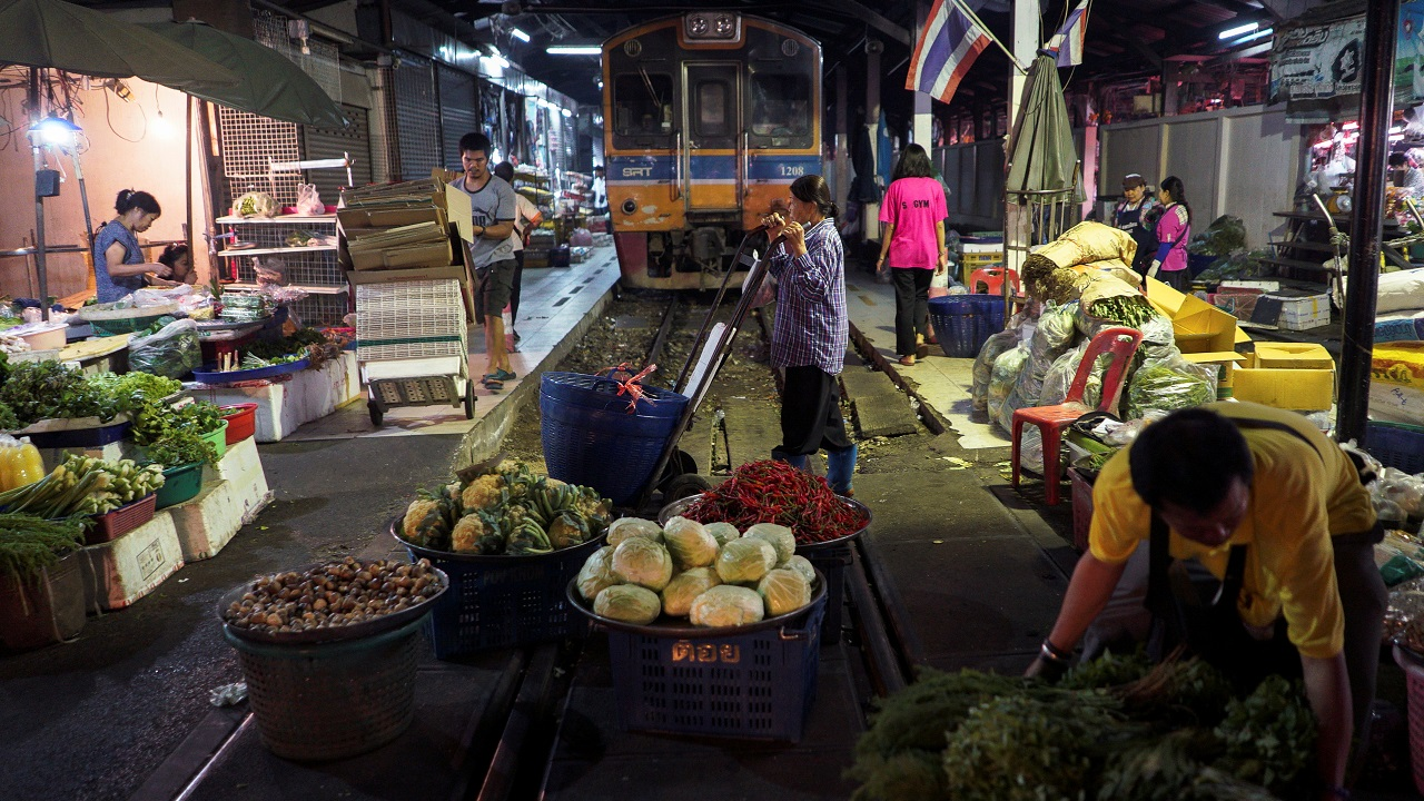 Vendors pull back their produce off a railway track to allow a cross-country train to dissect through the middle of the town of Machai in Samut Sakhon province, Thailand. (Reuters)
