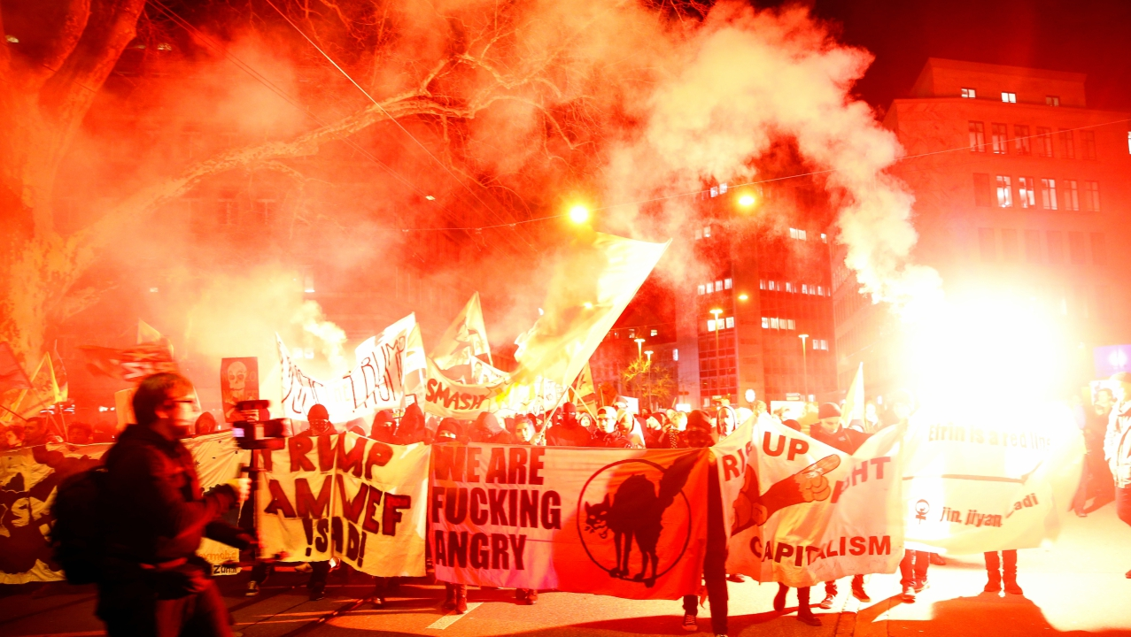 Protesters with banners light flares during a demonstration against U.S. President Donald Trump, ahead of Trump's visit to the World Economic Forum (WEF), in Zurich, Switzerland. (Reuters)