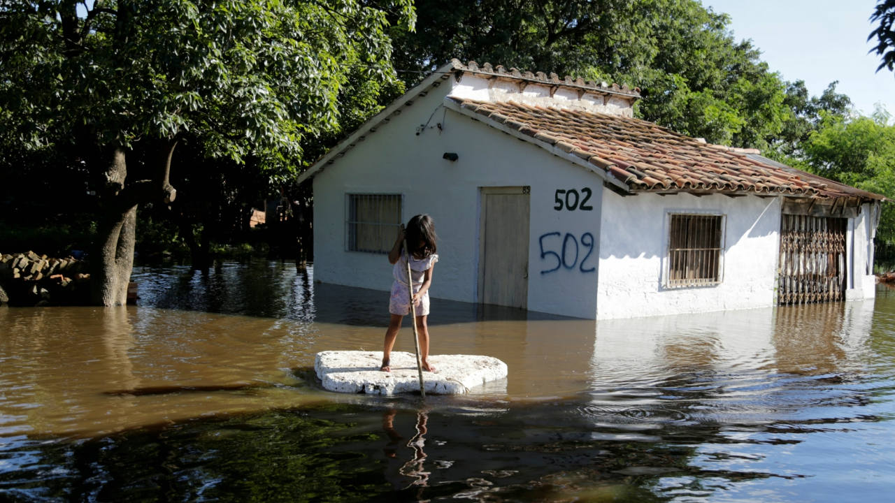A young girl uses a piece of styrofoam as a paddle board next to a flooded home after heavy rains caused the river Paraguay to overflow, on the outskirts of Asuncion, Paraguay. (Reuters)