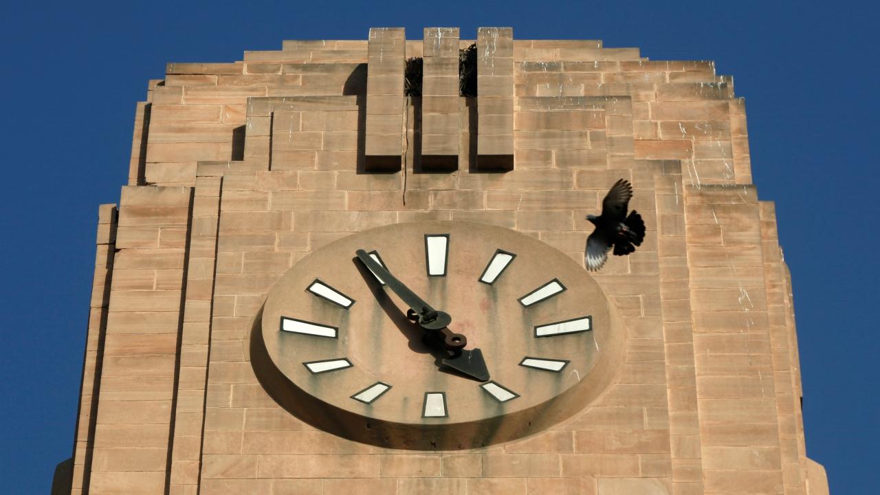 A pigeon flies past a stopped clock on the Lakshmi Building, built during the British Raj era, in Karachi, Pakistan. (Reuters)