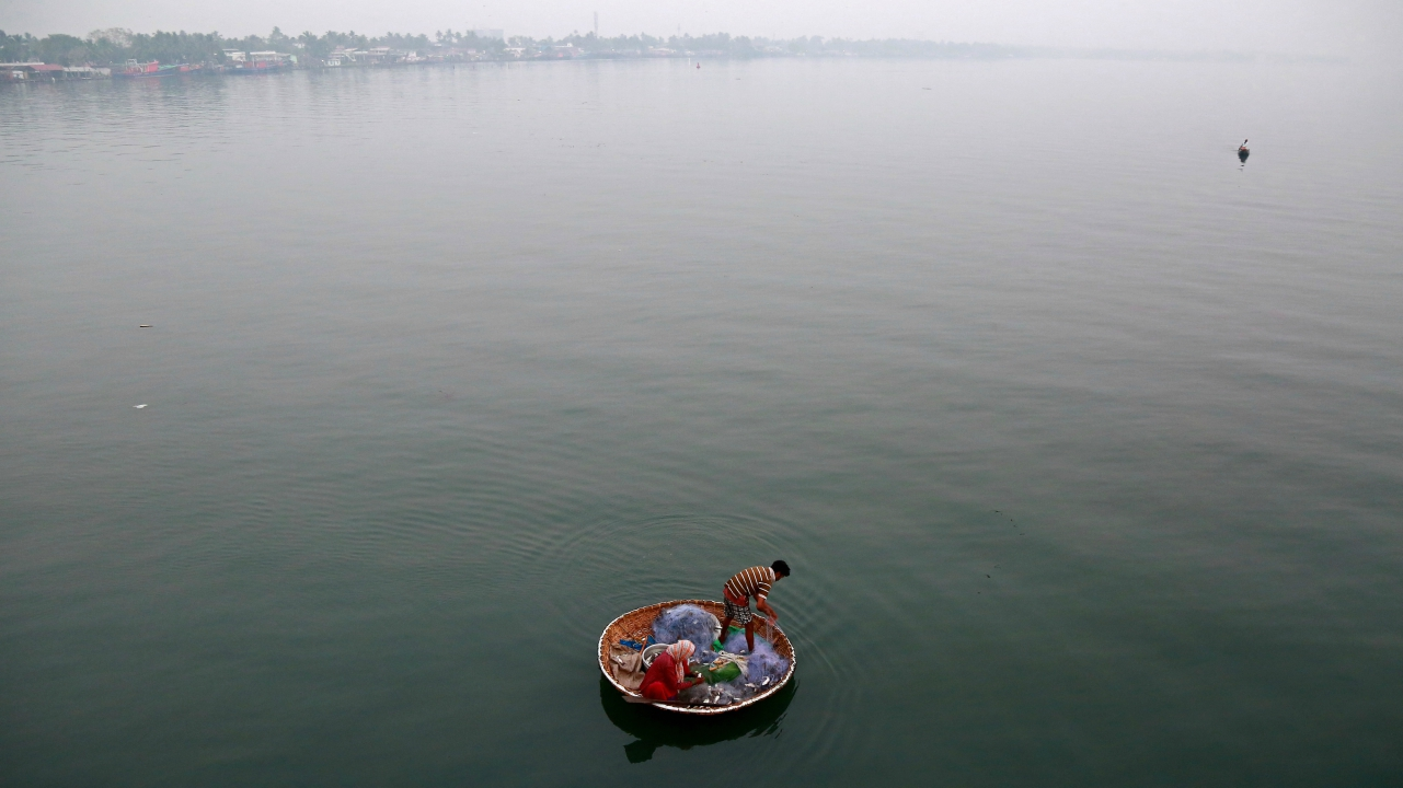 A fisherman and his wife catch fish in the waters of Vembanad Lake in Kochi, India. (Reuters)