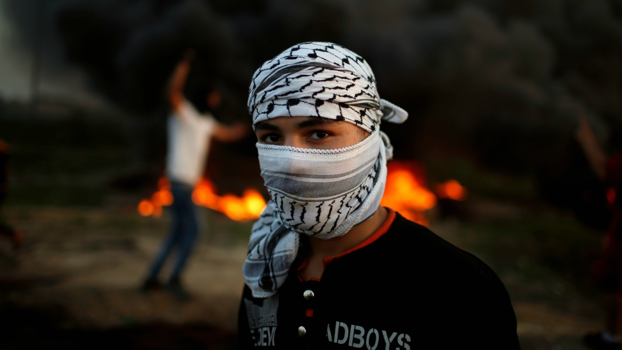 A Palestinian protester, who identified himself as Ahmed, poses for a photograph in front of burning tires at the scene of clashes with Israeli troops near the border with Israel, east of Gaza City. (Reuters)