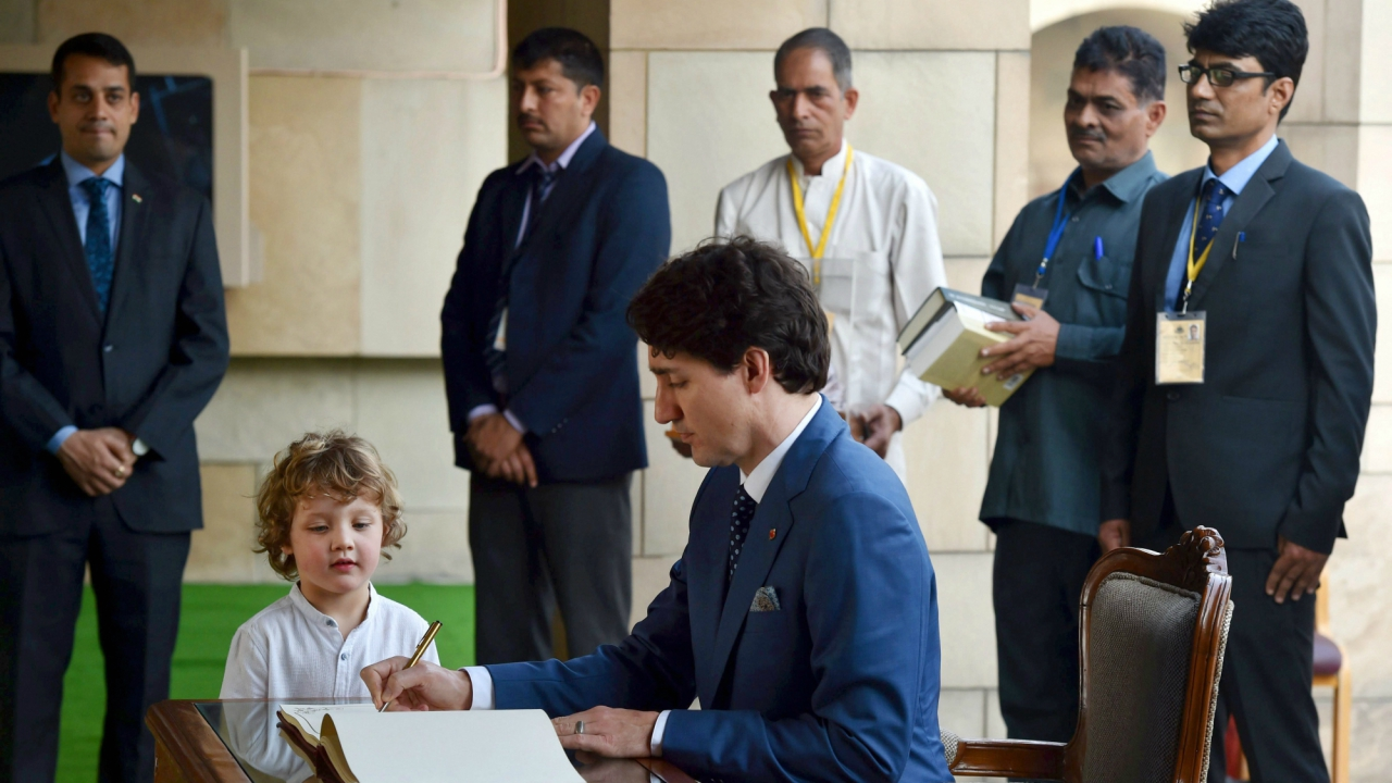 Canadian Prime Minister Justin Trudeau signs the visitor's  book as his son Hadrien looks on, after paying tribute at  Mahatma Gandhi's memorial Rajghat in New Delhi. (PTI)