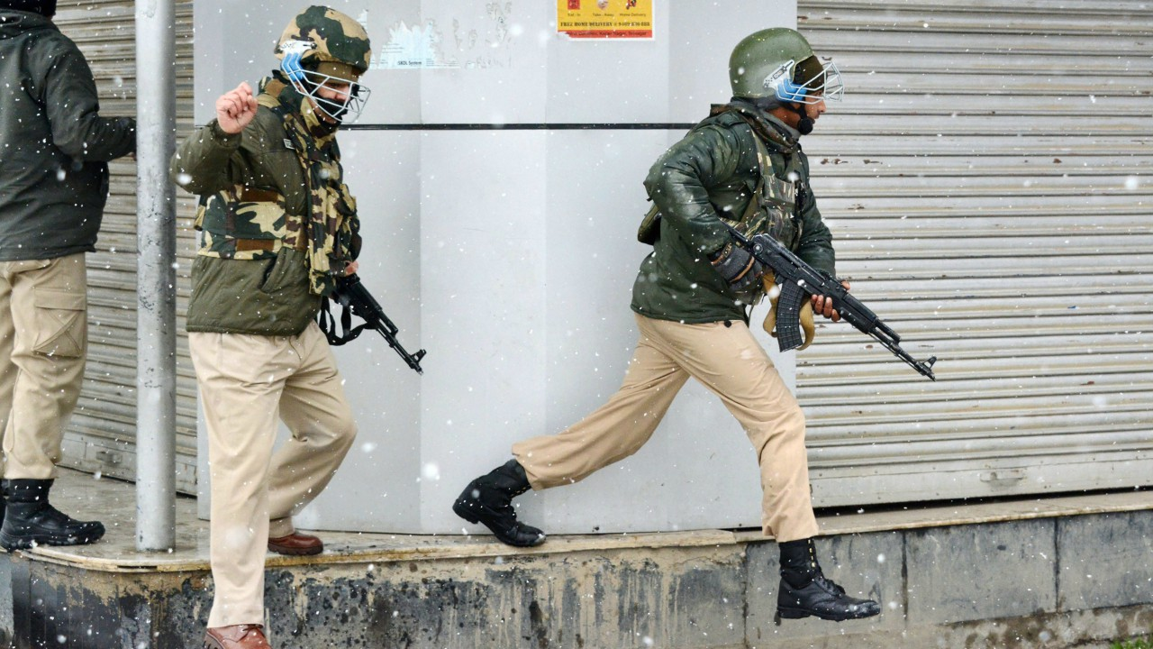 Security personnel take positions during an encounter with the militants, who were sheltering in a building near a CRPF camp at Karra Nagar, in Srinagar. (PTI)