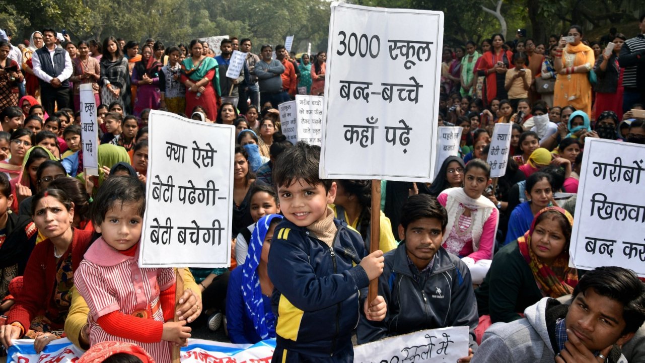 Parents, teachers and students display placards during a protest outside Delhi Chief Minister Arvind Kejriwal's residence, in New Delhi.  (PTI)