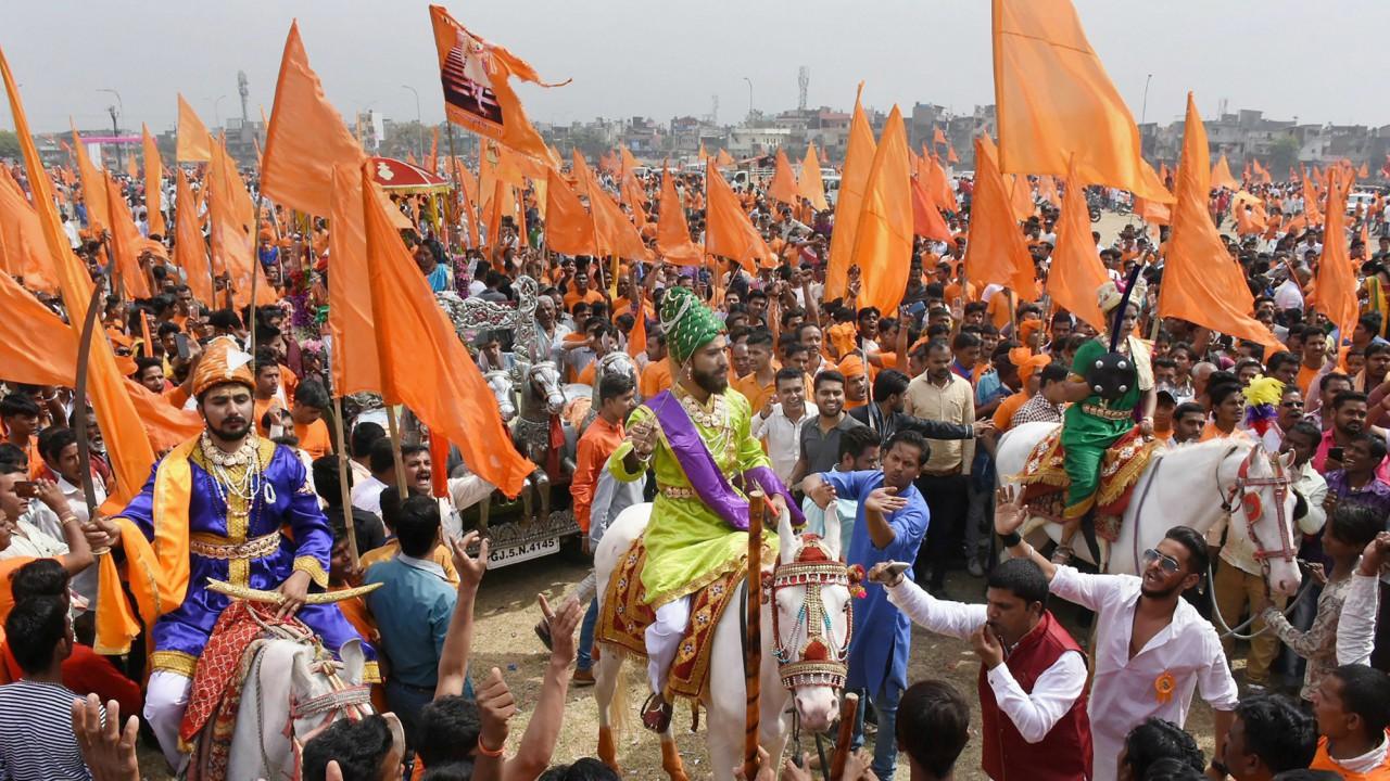 Artists raise flags and dress up in costume of Chhatrapati Shivaji as they celebrate Shivaji Jayanti in Surat. (PTI)