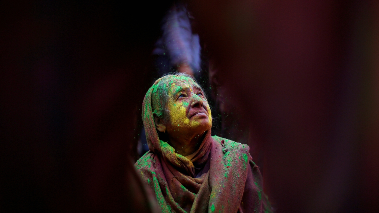 A widow daubed in colours takes part in Holi celebrations in the town of Vrindavan in the northern state of Uttar Pradesh, India. (REUTERS)