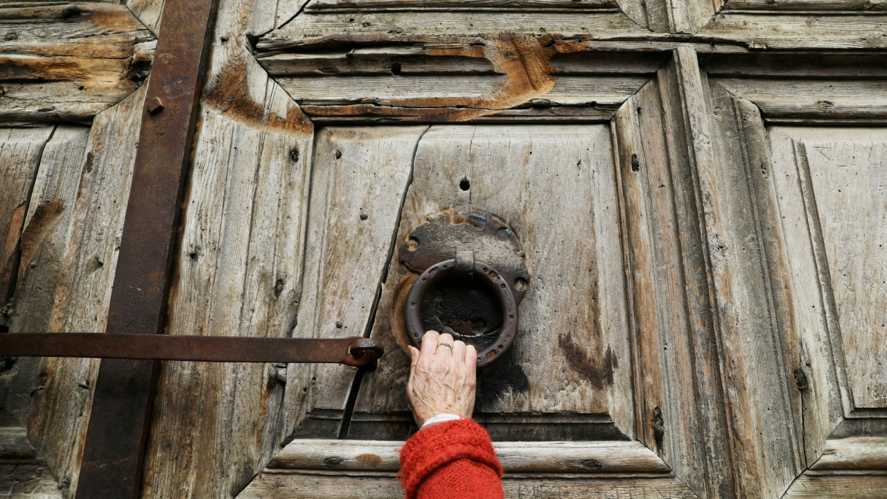 A worshipper touches the closed doors of the Church of the Holy Sepulchre in Jerusalem's Old City. (REUTERS)
