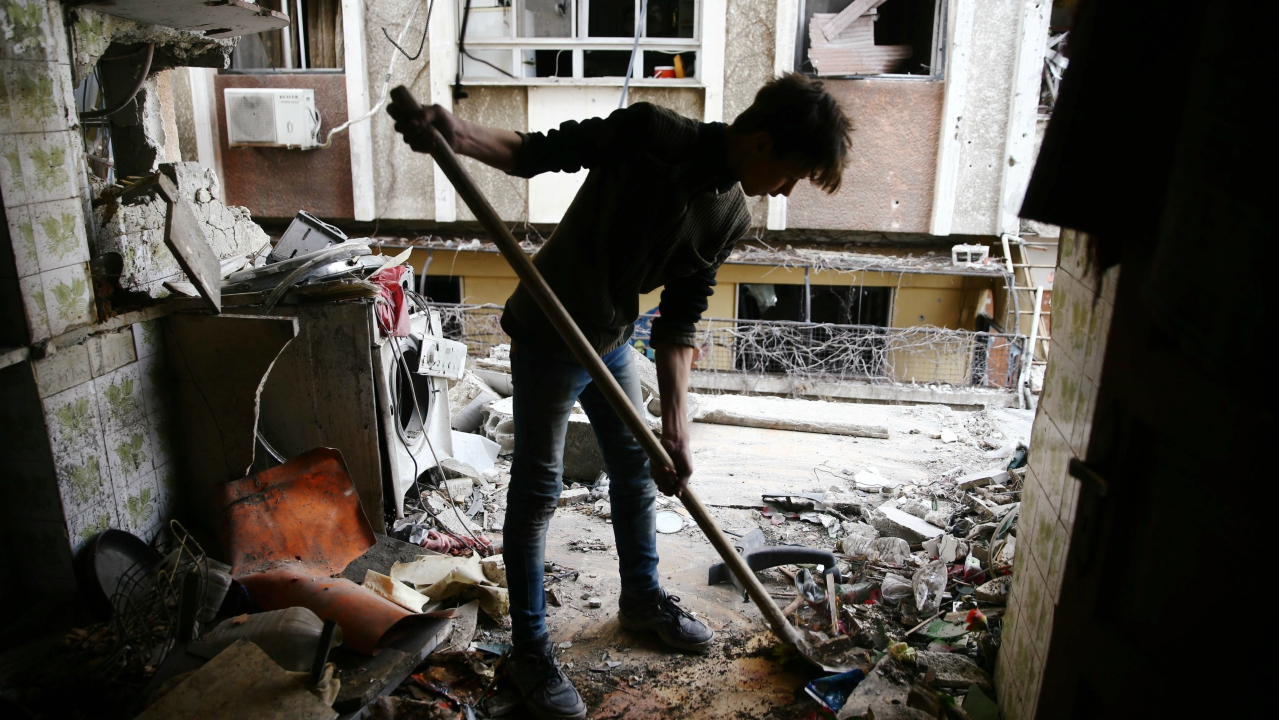 A young man cleans a damaged house in the besieged town of Douma, Eastern Ghouta, Damascus, Syria. (REUTERS)
