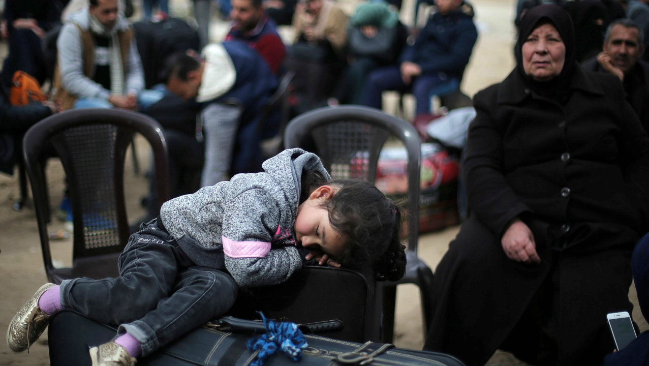 A girl sleeps on a suitcase as she waits with her family for a travel permit to cross into Egypt through the Rafah border crossing after it was opened by Egyptian authorities for humanitarian cases, in the southern Gaza Strip February 8, 2018. (Reuters)
