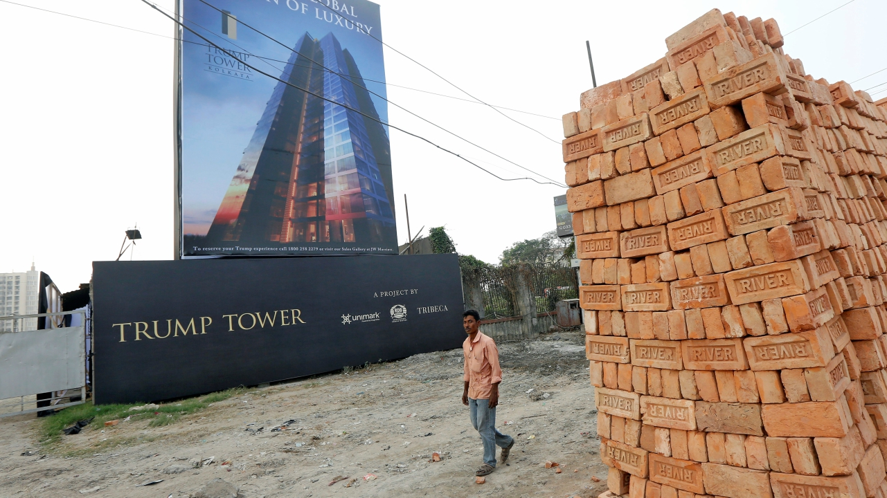 A man walks past a billboard of Trump Tower, a luxury apartment building, at a construction site in Kolkata, India. (Reuters)