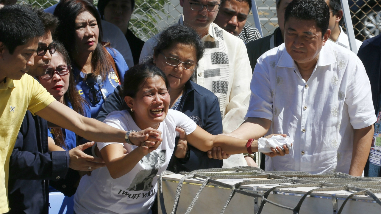 Jessica, center, and Jojit Demafelis, left, siblings of Joanna Demafelis who was found dead in a freezer in Kuwait, react as the wooden casket of her remains arrives at the Ninoy Aquino International Airport Friday, Feb. 16, 2018 in suburban Pasay city, southeast of Manila, Philippines. The death of Joanna, allegedly in the hands of a couple in Kuwait, prompted the populist President Rodrigo Duterte to order the repatriation of overseas Filipino workers from the oil-rich nation in the Middle East. Second from right is Foreign Affairs Secretary Alan Peter Cayetano. (AP/PTI)