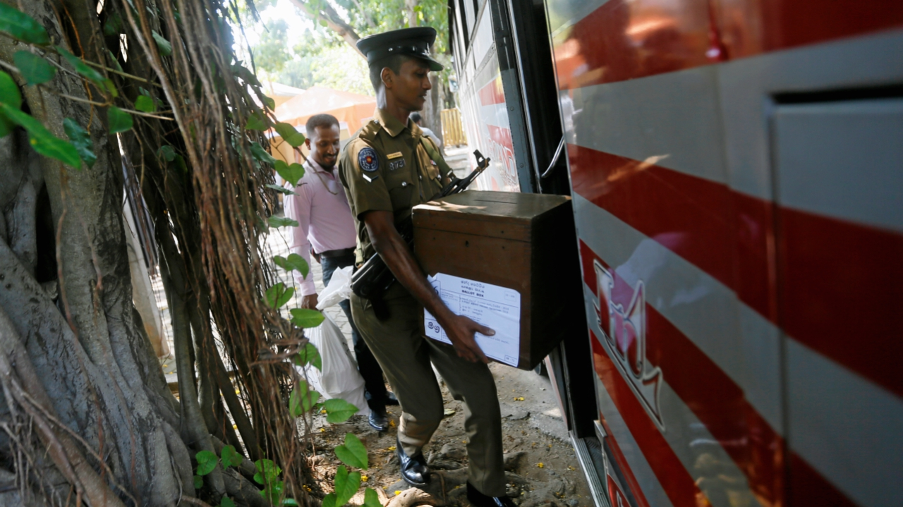 An electoral official carries a ballot box as he waits to get into a bus with a police officer ahead of local government polls in Colombo, Sri Lanka February 9, 2018.(Reuters)