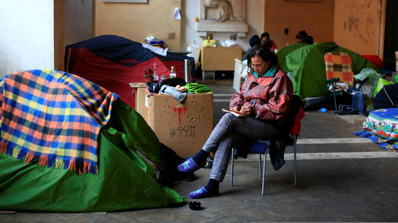 Angela Grossi sits next to her tent in the portico of the Basilica of the Santi Apostoli, where she lives after being evicted from an unused building along with other families in August 2017, in Rome, Italy. (Reuters)