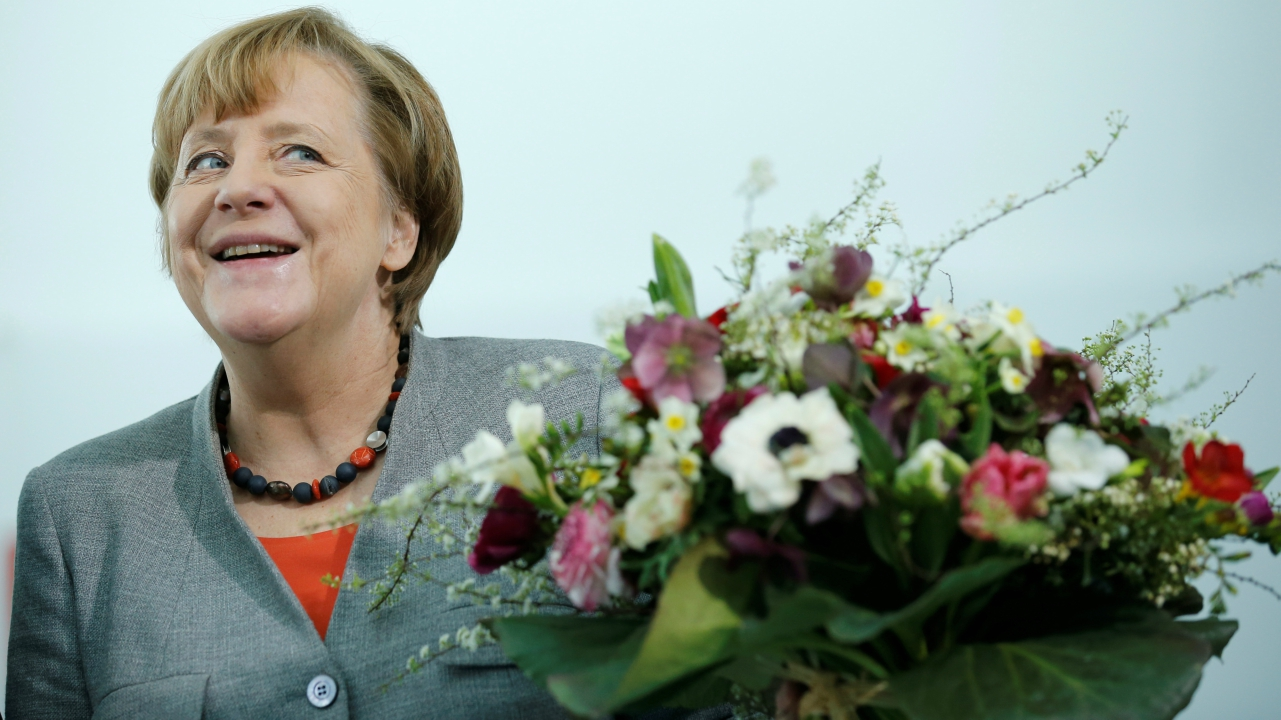 Chancellor Angela Merkel receives Valentine's Day flowers from the Central Gardening Association at the Chancellery in Berlin, Germany, February 9, 2018. (Reuters)