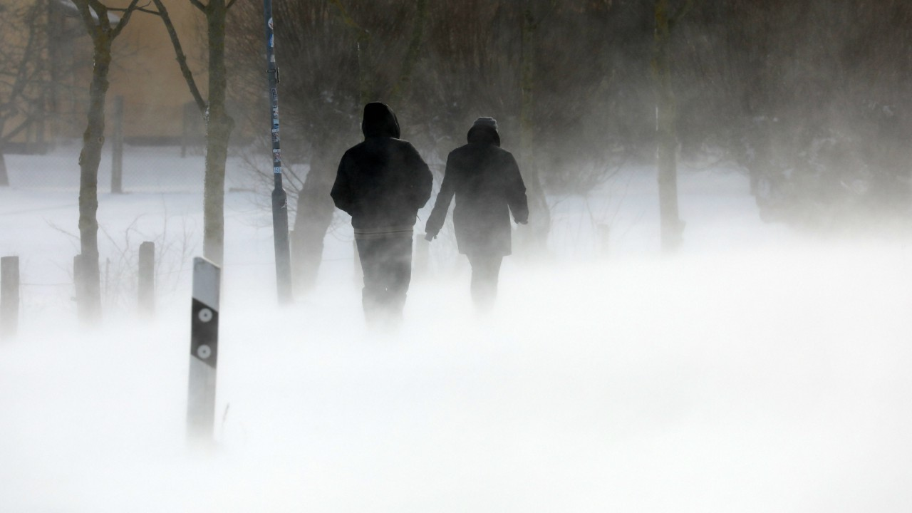 Ahrenshoop : dpatop - passer-bys walk along a snow-covered road during heavy snowfall in Ahrenshoop, Germany. (DPA/PTI)