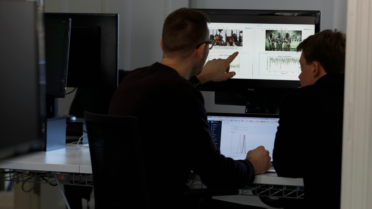 John Gibson (L), of ASI Data Science, demonstrates an illustration of how their newly designed software can distinguish between an ISIS extremist posting and a genuine news report, in London, Britain. (Reuters)