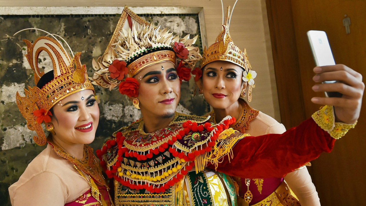 Indonesian artists dressed in their traditional attire take a selfie during an event to promote Indonesia tourism in Kolkata on Monday. (PTI)