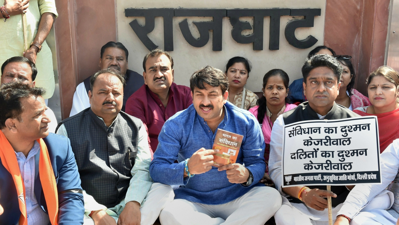 Delhi BJP President Manoj Tiwari with party supporters hold placards at a prayer meeting during 'Samvidhan ki Shapth' protest against Kejriwal government, at Rajghat in New Delhi, on Monday. (PTI)