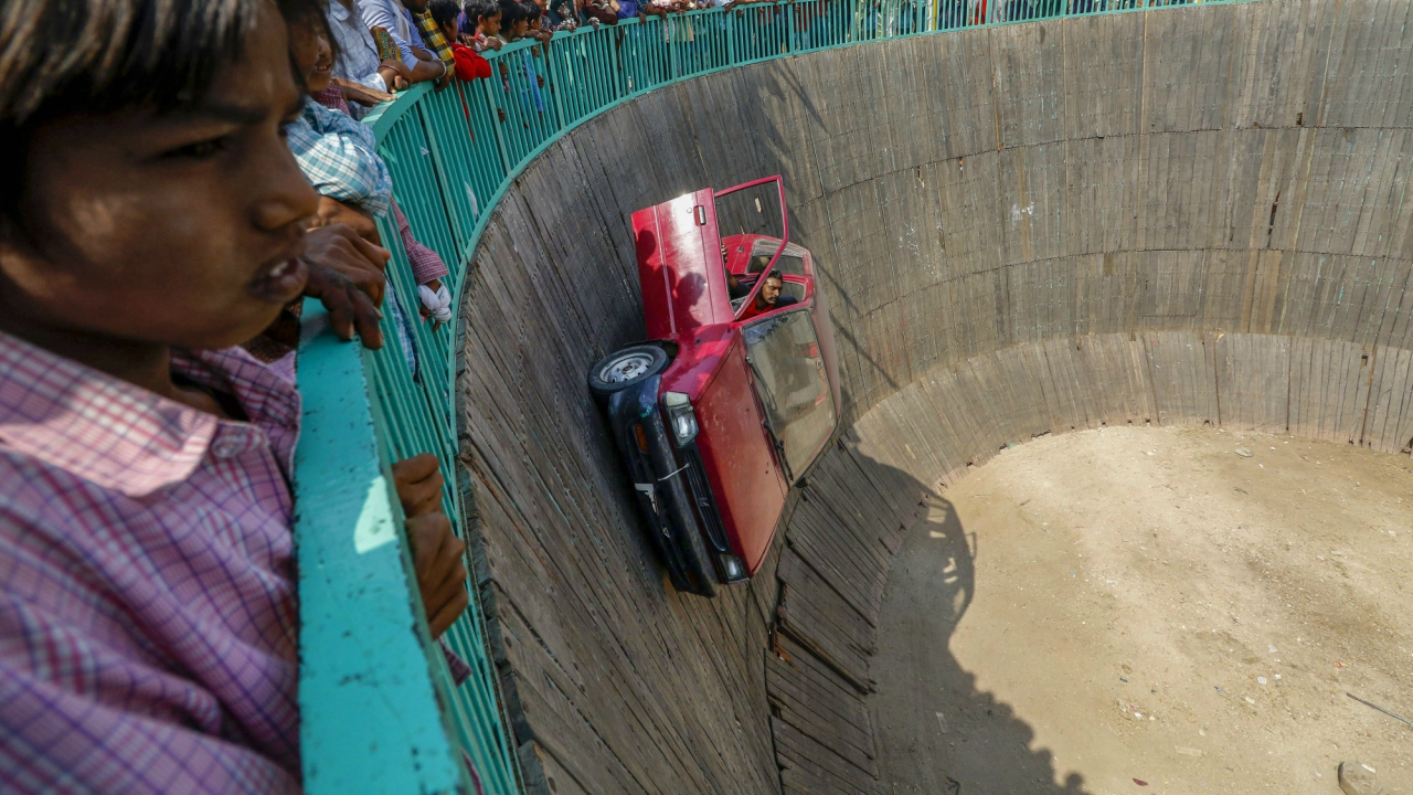 A stuntman rides his car inside a 'Well of Death' during 'Bhagoriya Ka Mela' ahead of Holi festival in Alirajpur on Monday. (PTI)