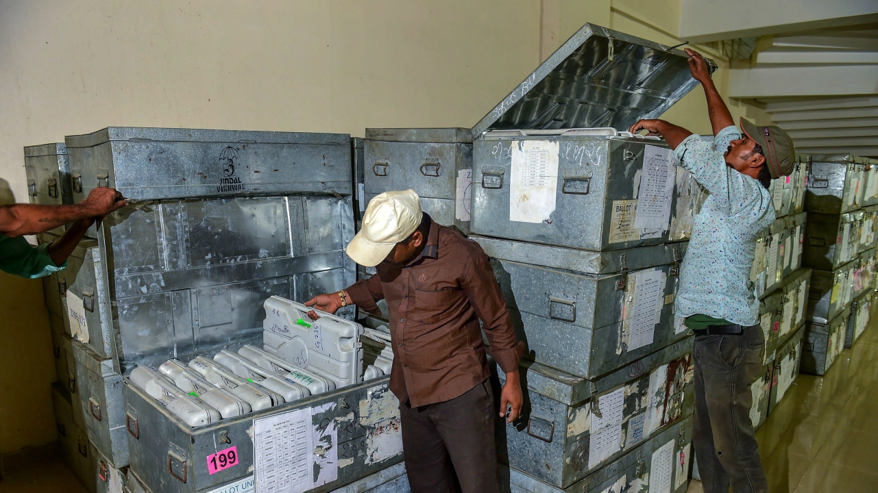 Workers arranging the boxes containing Electronic Voting Machines (EVM) as its arrive at the district collectors office from Gujarat for the upcoming  Karnataka elections, in Bengaluru. (PTI)