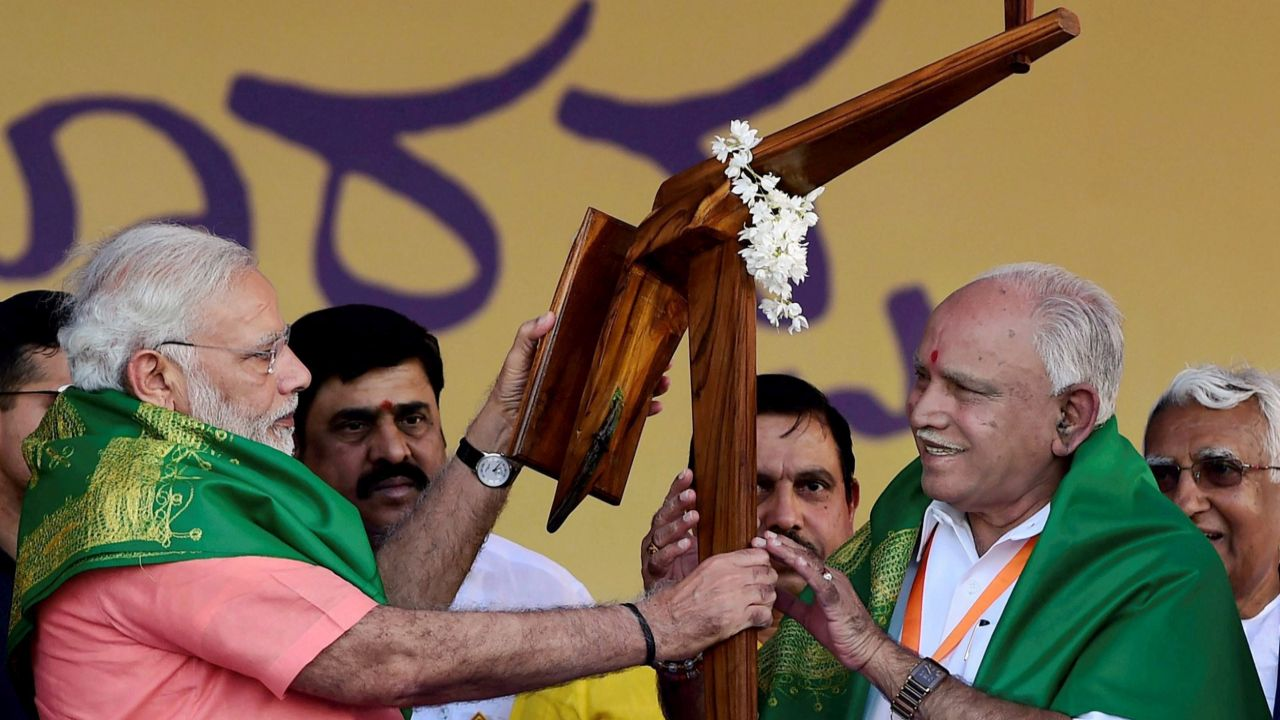 PM Narendra Modi hands over a model of plough to Karnataka BJP President and chief ministerial candidate B S Yeddyurappa during the party's 'Farmers Convention' at Davanagere in Karnataka. (PTI)