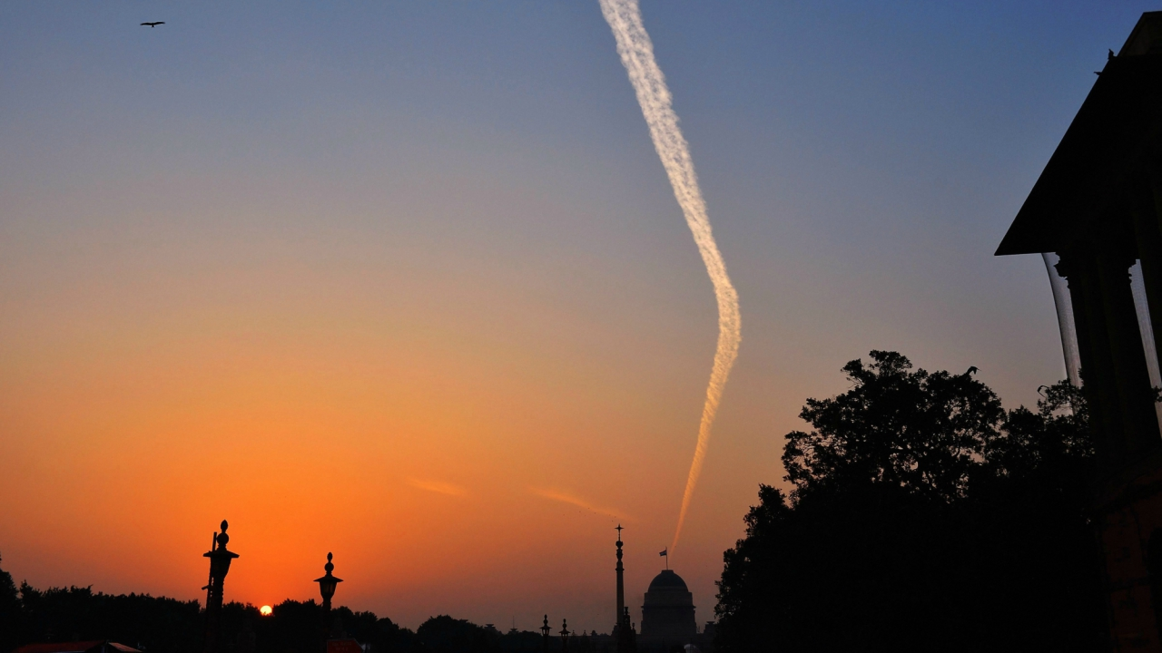 Aircrafts leave cloud trails, or contrails, in the sky over Raisina Hill during sunset in New Delhi on Friday. (PTI)