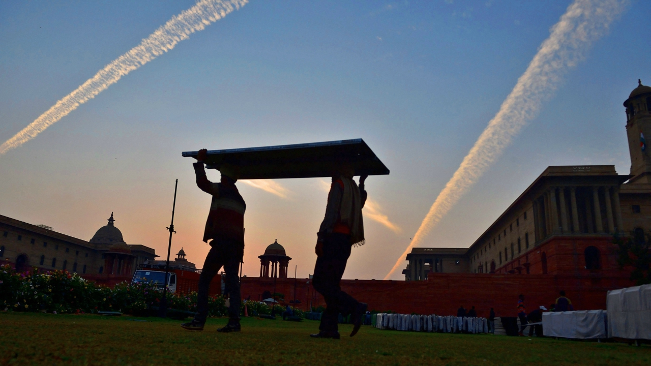 Workers dismantle Republic Day stands as aircrafts leave cloud trails, or contrails, in the sky over Raisina Hill during sunset in New Delhi on Friday. (PTI)