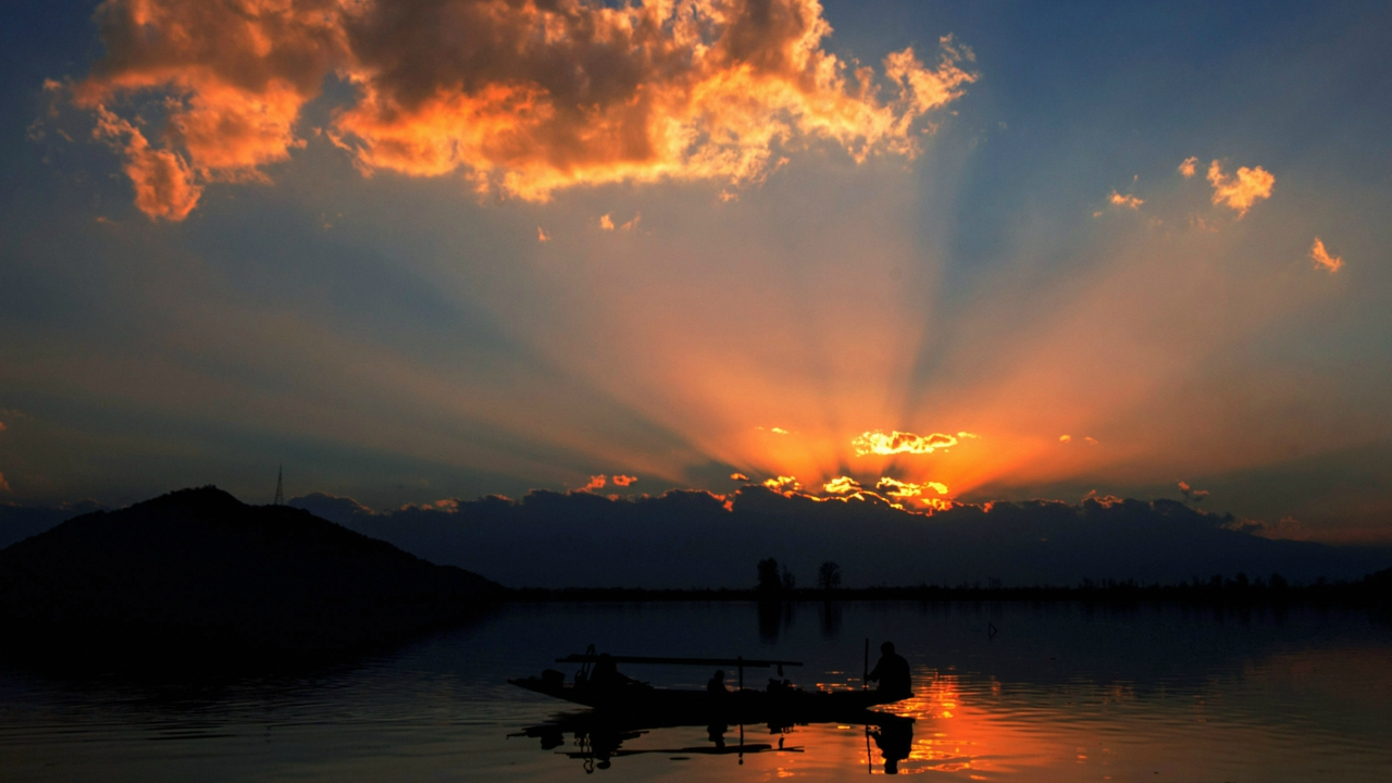 A fisherman with his family rows his boat during sunset in Dal Lake, Srinagar on Sunday. (PTI)