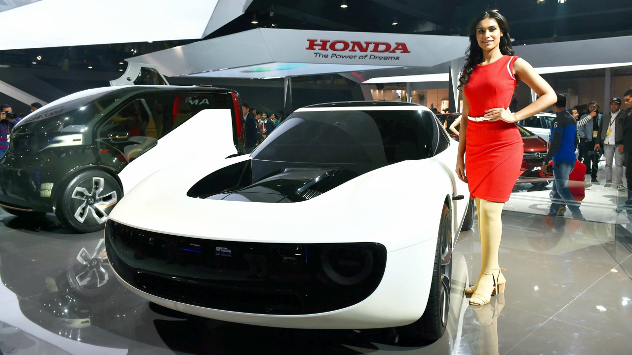 A model poses next to a concept car at a stall at the Auto Expo 2018 in Greater Noida (PTI)