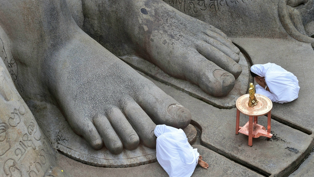 Devotees offer prayers near the 57-foot-high monolithic Gomateshwara statue on Vindyagiri in Shravanabelagola, around 160 km west of Bengaluru on Wednesday. Thousands of Jain devotees will attend the Mahamastakabhisheka (head anointing ceremony) on February 17. (PTI)