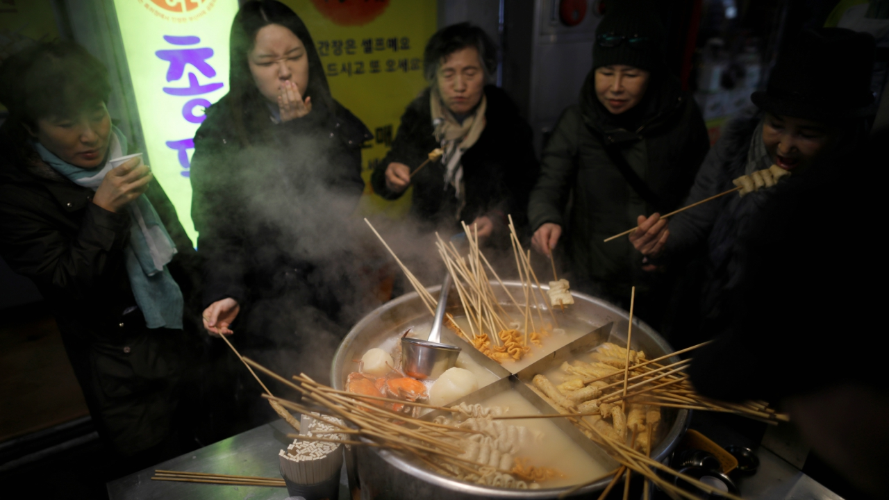 People eat fishcakes at a traditional market in Gangneung, South Korea. (Reuters)