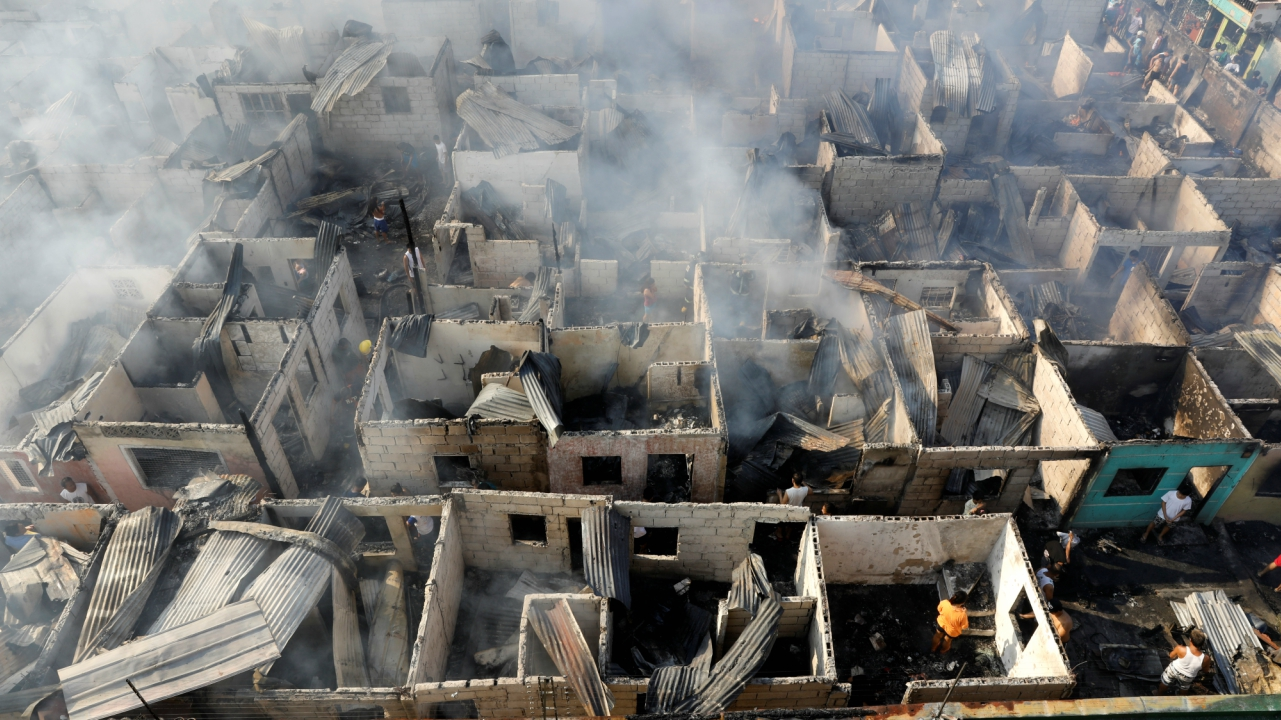 Fire victims sift through the ruins of their houses that were gutted by a fire in Paranaque, Metro Manila, Philippines. (Reuters)