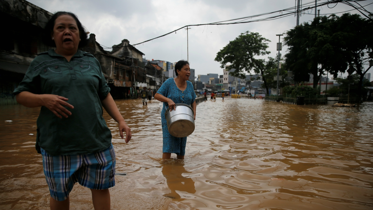 Women wade through a flooded street in Jatinegara district in Jakarta, Indonesia. (REUTERS)