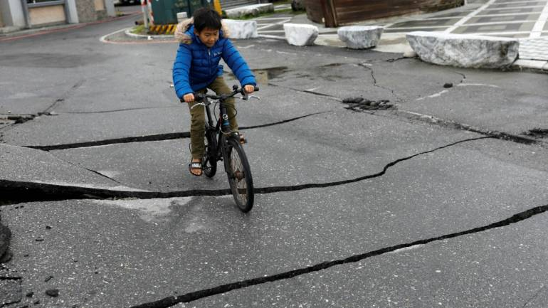 A child rides a bicycle on a fractured road after an earthquake hit Hualien, Taiwan February 8, 2018. (Reuters)