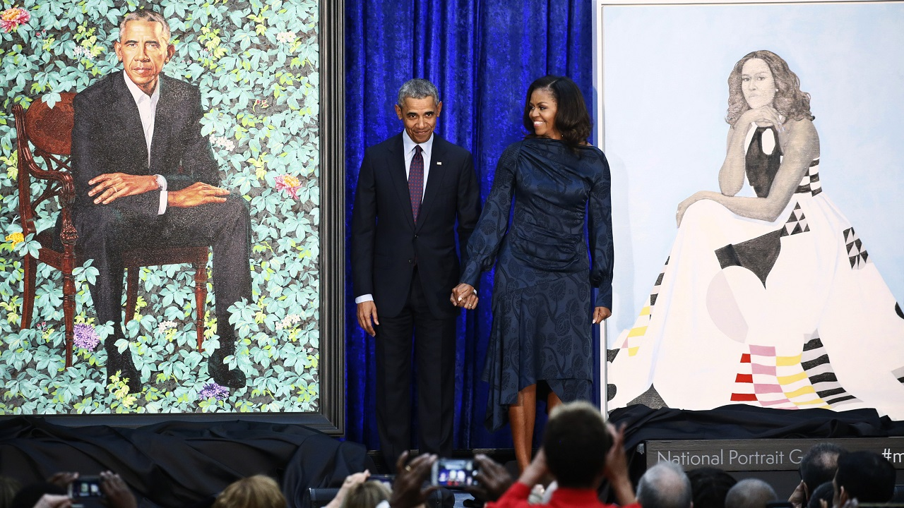 Barack Obama and Michelle Obama hold hands between their portraits. (Reuters)