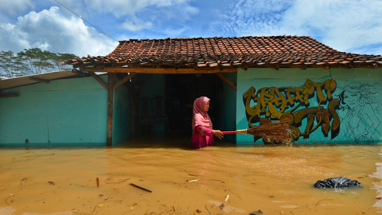 A woman villager cleans garbage in front of her house as flood hits Tanjungsari village in Tasikmalaya, Indonesia. (REUTERS)