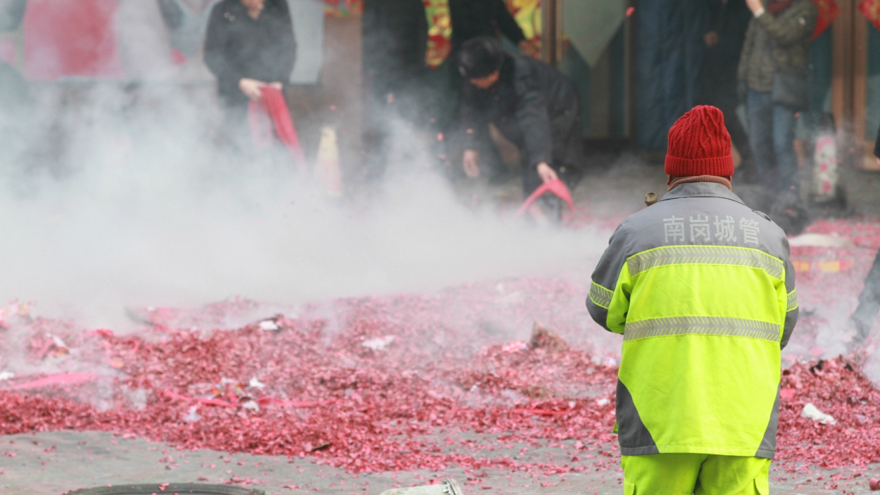 A sanitation worker stands amid heavy smog as shop owners set off firecrackers and fireworks to pray for good business, after Spring Festival holidays, in Harbin, Heilongjiang province, China. (REUTERS)