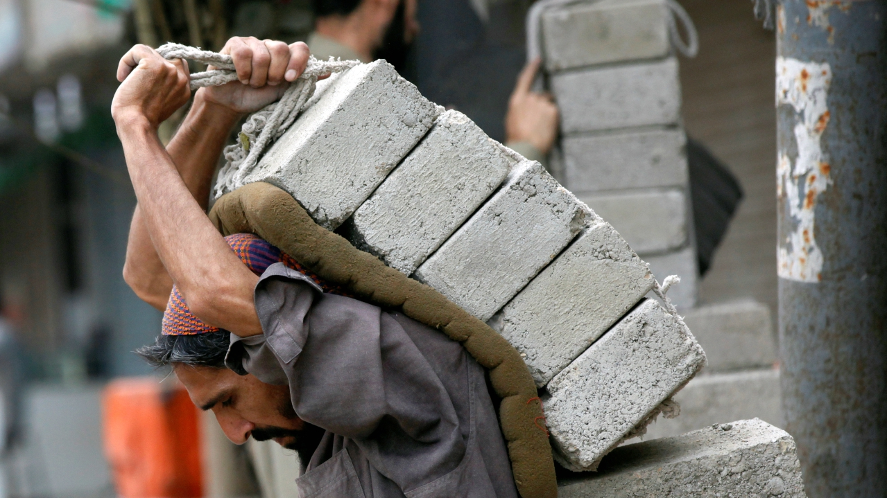 A labourer carries bricks on his back at a construction site in Karachi, Pakistan. (REUTERS)