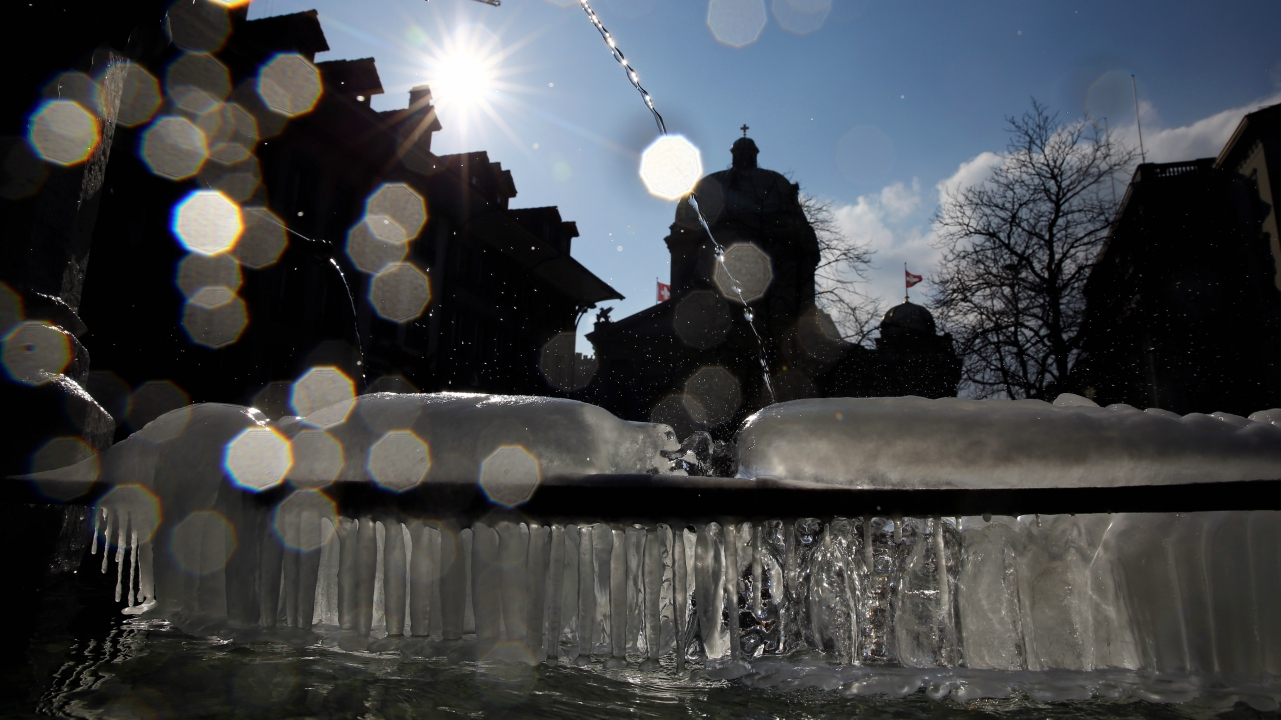 The Swiss Federal Palace (Bundeshaus) is seen behind a fountain partially covered with ice in Bern, Switzerland. (REUTERS)