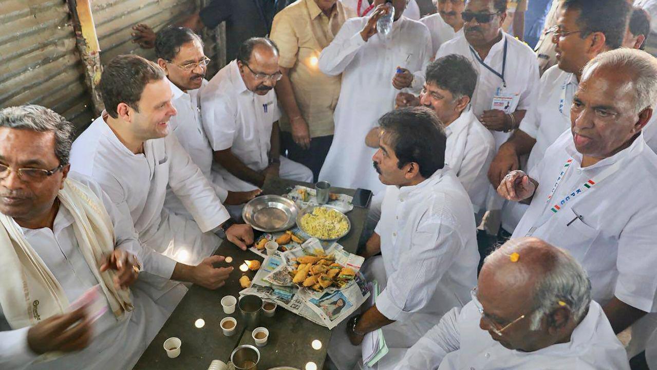 Congress President Rahul Gandhi, along with Karnataka Chief Minister Siddaramaiah and party leaders has 'Mirchi Bajji', a local 'pakora' snack, along with tea at Kalamala, 16 kms from Raichur on Monday. (PTI)