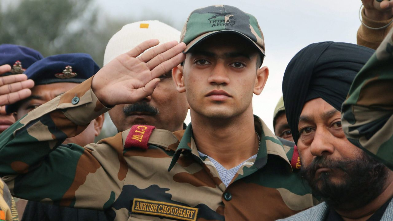 Ankush, son of Indian Army JCO Madan Lal Choudhary, who was killed in the terrorist attack at Sunjuwan Army camp, salutes his father's mortal remains. (PTI)