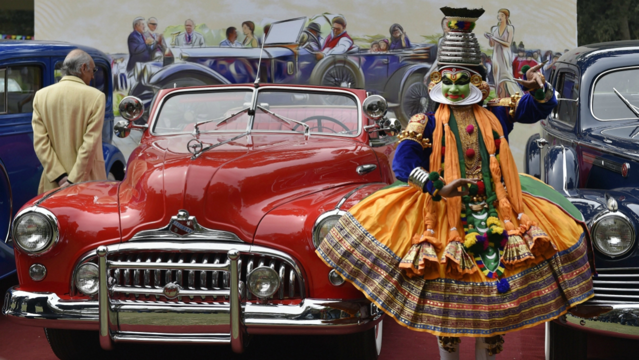 Artists pose with vintage cars during a media preview for the upcoming 21 Gun Salute International Vintage Car Rally & Concours Show, in New Delhi, on Tuesday. (PTI)
