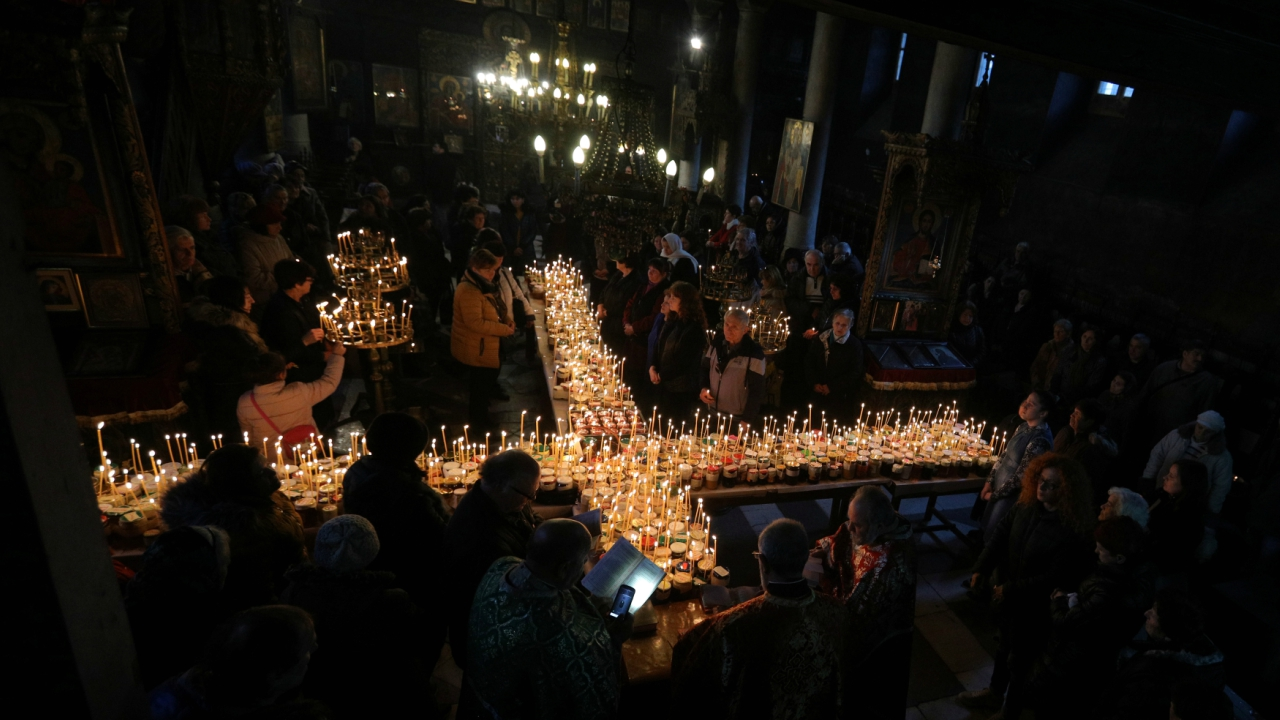 Worshippers gather around candles stuck to jars with honey, during a religious mass in the church of the Presentation of the Blessed Virgin in Blagoevgrad, Bulgaria February 9, 2018. The day of Saint Haralampi, the Orthodox patron saint of beekeepers, is marked on Friday.(Reuters)