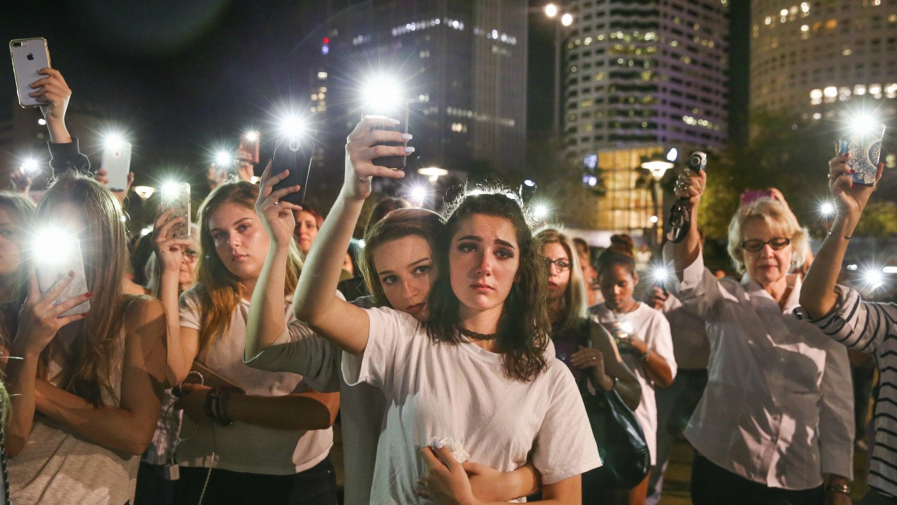 Mary Claire Foley, center left, 16, embraces Ariana Skafidas, 16, students at Henry B. Plant High School at Curtis Hixon Park in downtown Tampa as they raise their lights during a vigil to honor victims of Wednesday's shooting at Marjory Stoneman Douglas High School in Parkland, Florida. (AP/PTI)