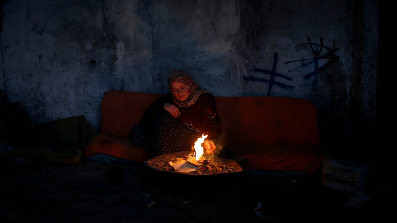 A Palestinian woman warms herself by a fire inside her house on a winter day, in the northern Gaza Strip. (REUTERS)